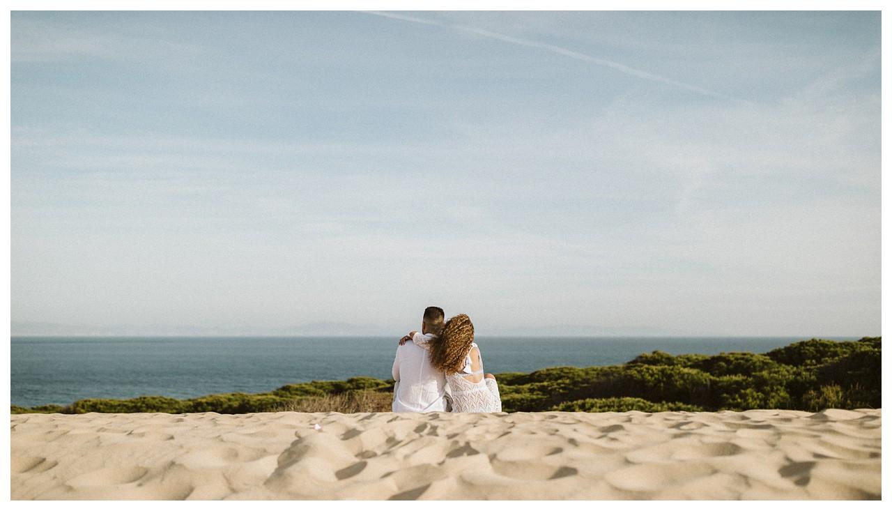 Una pareja mirando el horizonte en la playa